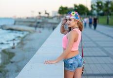 La giovane ragazza bionda sexy negli shorts del denim sta su lungomare della città ed esamina il mare Immagini Stock