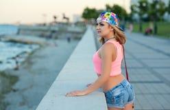 La giovane ragazza bionda sexy negli shorts del denim sta su lungomare della città ed esamina il mare Fotografia Stock