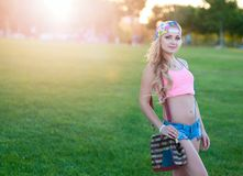 La giovane ragazza bionda sexy negli shorts del denim sta su un prato inglese in un parco dell'estate Fotografie Stock Libere da Diritti