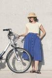 La giovane ragazza bionda sexy sta stando vicino alla bicicletta Immagine Stock