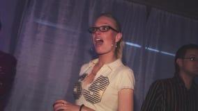 La giovane ragazza bionda in vetri gode del partito in night-club incoraggiare Dancing e canto intrattenimento archivi video