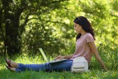 La giovane ragazza castana con il computer portatile all'aperto sta lavorando Fotografie Stock Libere da Diritti
