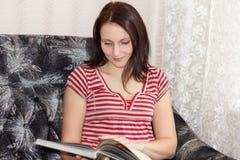 La giovane ragazza castana legge un libro che si siede sul sofà e sul sorridere immagini stock