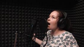 La giovane ragazza caucasica con capelli scuri lunghi è canzone romantica di canto appassionato Cantante femminile di schiocco at stock footage