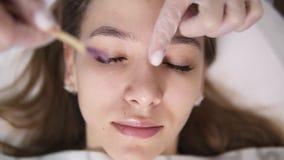 La giovane, ragazza caucasica sta trovandosi sullo strato durante il trattamento dei eyebrowes a bellezza dello studio, estetista archivi video
