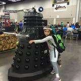 La giovane ragazza costumed abbraccia il carattere di BBC Dalek immagini stock