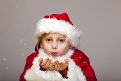 La giovane ragazza del Babbo Natale salta i fiocchi della neve dalla palma Fotografie Stock