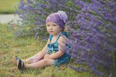 La giovane ragazza del bambino di bellezza che posa nel prato di Central Park vicino ai jeans d'uso del cespuglio del lavander si fotografie stock libere da diritti
