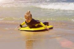 La giovane ragazza del surfista con il bodyboard cammina lungo la spuma del mare della spiaggia Fotografia Stock