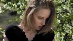 La giovane ragazza del tander sta abbracciandosi in parco di giorno di estate, guardante alla macchina fotografica, albero della  archivi video