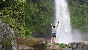 La giovane ragazza del viaggiatore prende l'innalzamento su delle armi alla cascata stupefacente della giungla in Bali, Indonesia video d archivio