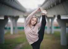 La giovane ragazza dell'acrobata in maglia con cappuccio beige esegue l'allungamento stare su una gamba contro lo sfondo del pont fotografia stock