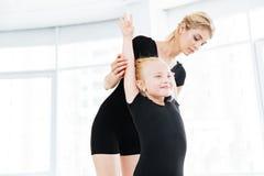 La giovane ragazza della ballerina che fa l'allungamento si esercita con il suo insegnante femminile Fotografie Stock Libere da Diritti