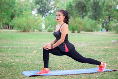La giovane ragazza di forma fisica allunga le gambe durante l'allenamento di addestramento Fotografie Stock Libere da Diritti