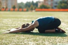 La giovane ragazza di forma fisica osserva in camicia blu e ghette che fanno l'allungamento nel tramonto Campo di football americ Immagini Stock