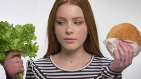 La giovane ragazza dolce dello zenzero sta scegliendo fra sano ed alimento non sano, scelga la lattuga, fondo bianco archivi video