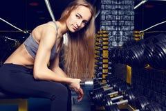 La giovane ragazza esile che fa il bicipite arriccia con le teste di legno Fotografie Stock