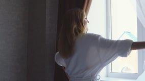 La giovane ragazza felice in abito bianco guarda fuori la finestra nelle tende di apertura e di primo mattino video d archivio