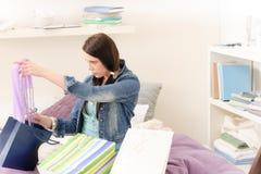 La giovane ragazza felice dell'allievo disimballa i sacchetti di acquisto Immagine Stock