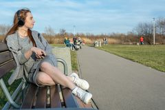 La giovane, ragazza felice della testarossa in primavera nel parco vicino al fiume ascolta musica tramite le cuffie senza fili de fotografia stock