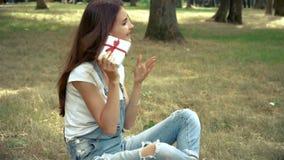 La giovane ragazza felice tiene e tratta il regalo che si siede fuori stock footage