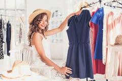 La giovane ragazza graziosa che sceglie e che prova sui vestiti al negozio immagini stock