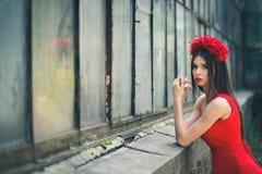 La giovane ragazza graziosa sta posando con i fiori Fotografie Stock Libere da Diritti