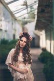 La giovane ragazza graziosa sta posando con i fiori Fotografia Stock