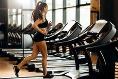 La giovane ragazza mora atletica si ? vestita negli sport neri superiori e mette le calorie in cortocircuito delle ustioni sulla  fotografia stock