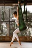 La giovane ragazza mora esile vestita in cima e calzamaglia bianche di sport sta facendo allungando l'esercizio sull'amaca verde immagini stock libere da diritti