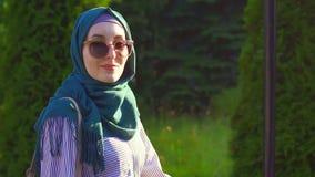 La giovane ragazza musulmana attraente nel hijab va ed esamina la macchina fotografica Mo lento archivi video