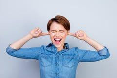 La giovane ragazza pazza sta gridando con gli occhi chiusi e le orecchie Lei doesn Fotografia Stock Libera da Diritti