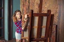 La giovane ragazza piacevole dell'adolescente sta piegando sul molbert nello studio di arte fotografia stock libera da diritti