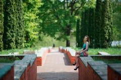 La giovane ragazza piacevole si siede su una protezione della scala Immagini Stock Libere da Diritti
