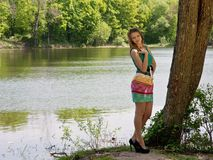 La giovane ragazza piacevole snella in un'ombra dell'albero Fotografie Stock Libere da Diritti