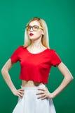 La giovane ragazza seria che indossa il brevi agrostide bianco ed occhiali sta posando su fondo verde Ritratto della bionda grazi fotografia stock libera da diritti
