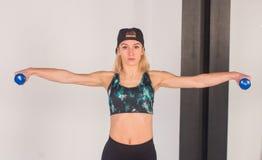 La giovane ragazza sexy di atletica che fa le teste di legno preme gli esercizi La forma fisica muscled la donna nell'allenamento Immagine Stock
