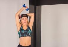 La giovane ragazza sexy di atletica che fa le teste di legno preme gli esercizi La forma fisica muscled la donna nell'allenamento Fotografie Stock