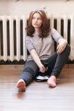 La giovane ragazza sexy si siede sul pavimento con una leva di comando del gioco fra le gambe Fotografie Stock