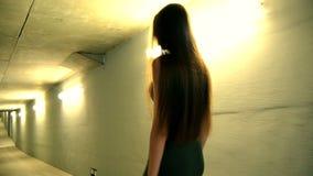 La giovane ragazza snella va nella sera su una via vuota video d archivio