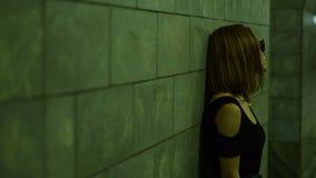 La giovane ragazza sola in vetri e maglietta neri sta in un sottopassaggio stock footage