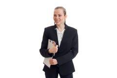 La giovane ragazza sorridente nel vestito nero dell'ufficio tiene la cartella nelle mani Immagini Stock Libere da Diritti