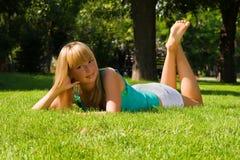 La giovane ragazza sorridente si trova su erba Immagine Stock