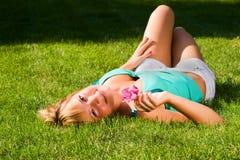 La giovane ragazza sorridente si trova su erba sulla parte posteriore Fotografia Stock