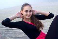 La giovane ragazza sportiva fa gli esercizi dell'ABS durante la forma fisica che forma il ou Fotografia Stock