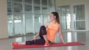 La giovane ragazza sportiva fa l'esercizio d'allungamento difficile sulla stuoia della palestra mentre si prepara nella palestra Immagini Stock Libere da Diritti