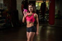 La giovane ragazza sportiva nel corridoio di forma fisica sta tenendo un agitatore dell'acqua, forma fisica Immagine Stock