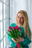La giovane ragazza sveglia con il mazzo di molla fiorisce la festa, l'8 marzo, delle donne internazionali sorridenti Fotografia Stock Libera da Diritti
