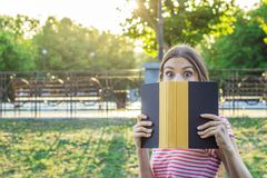 La giovane ragazza sveglia copre il suo fronte di libro Donna sorpresa e colpita Ragazza emozionale che tiene un libro in sue man Immagine Stock
