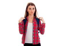 La giovane ragazza sveglia in una camicia di plaid e con una cartella sui supporti posteriori diritto e esamina una macchina foto Immagini Stock